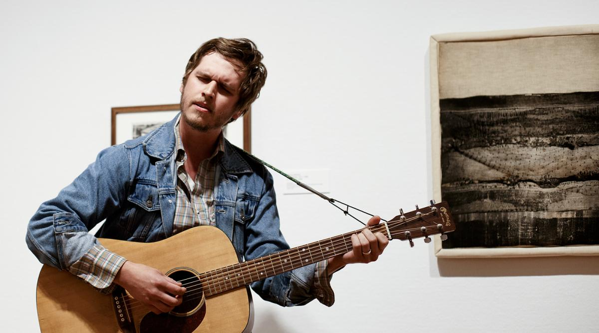 Image of a man in his 30s wearing a collared shirt and singing while playing an acoustic guitar. He stands before a work of art that depicts a prairie landscape. It is stitched or quilted onto cloth and framed. He is singing in an art gallery.