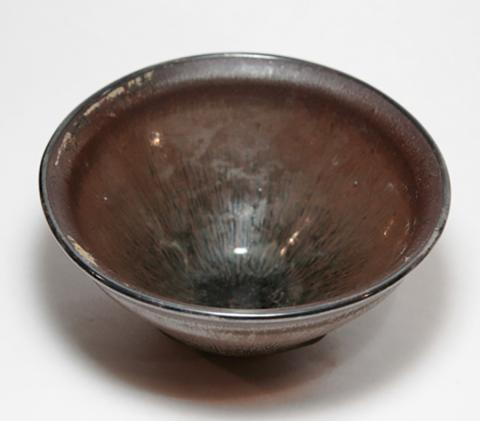 Small brown tea bowl that could fit in a person's hand. Glaze is grey in the middle and deeper brown at edges, with silver on the rim. Surface is smooth. This bowl is around 700 years old.