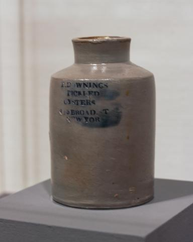 "Cylindrical oyster jar with a narrow neck, made of grey glazed ceramic. It stands 6-8 in tall and has writing stamped on it, highlighted with cobalt blue glaze. ""T. Downings Pickeld Oysters, No. 5 Broad St. New York"""