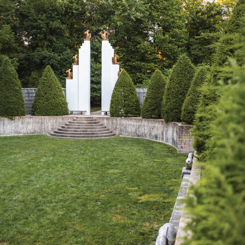 a portion of an oval, walled lawn with steep embankments that are planted with conical evergreen trees all around. At the far end, there are stairs that lead up and out of the garden; its exit is flanked by giant, columns symmetrical on  either side