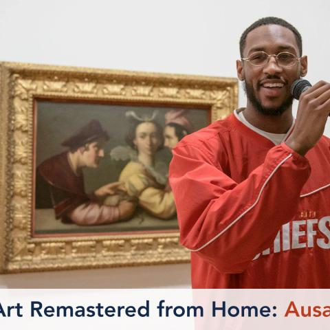 A musician stands behind a microphone, smiling. He is in front of a painting of two men and a woman.