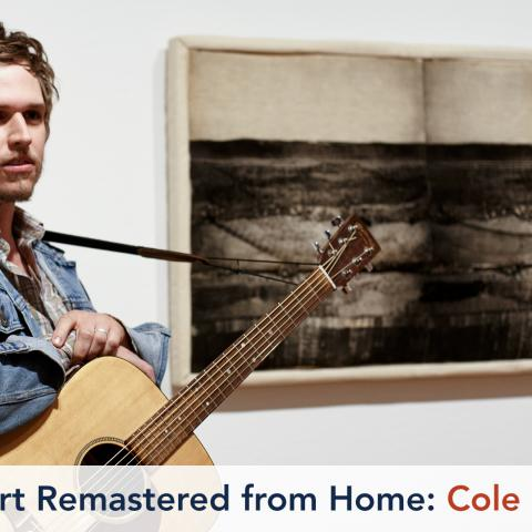 A man with an acoustic guitar stands next to an artwork made of printed and stuffed fabric.