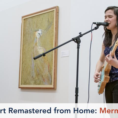 A musician plays an electric guitar in front of a painting. She is playing to a crowd seated on the floor.