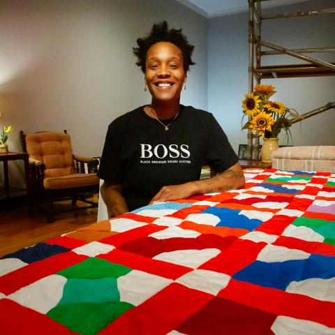 Portrait of a young Black woman smiling in an art gallery, Before her is a brightly colored quilt and in the background art is installed on the walls with comfy furnishings for sitting, like a home setting.